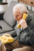 senior man talking on retro phone at home