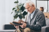 Fotografie senior man holding shoes in hands while sitting on sofa
