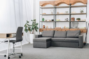 modern living room with sofa, racks and workspace