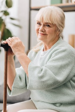 cheerful senior woman smiling and holding walking stick
