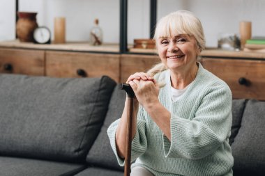 cheerful senior woman sitting on sofa and holding walking stick