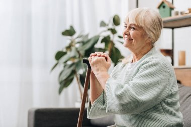 cheerful retired woman smiling and holding walking stick