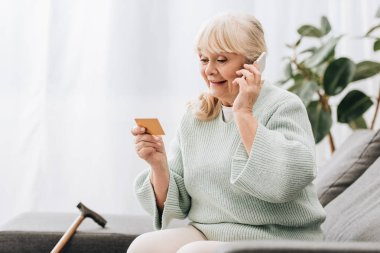 smiling blonde retired woman looking at credit card while talking on smartphone