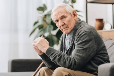 sad pensioner sitting on sofa in living room