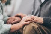 oříznutý pohled důchodci pár, drželi se za ruce