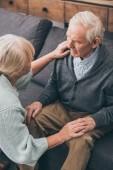 starší pár, drželi se za ruce a díval se na sebe doma
