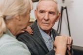 Selektivní fokus smutný důchodce při pohledu na bývalý ženu doma