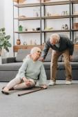 Starší žena sedí na podlaze s bolestí v koleně poblíž bývalý manžel