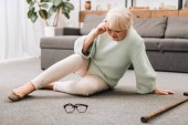 Donna pensionata che si siede sul pavimento vicino a vetri e camminare canna e avendo mal di testa
