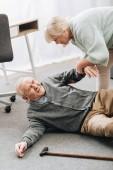 stará žena pomáhá postavit se manžel který protrhla na podlaze s vycházkovou holí