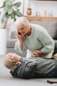 Starší žena pomáhající manžela který protrhla na podlaze a držení ruky