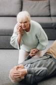 Starší žena pomáhá stará manžel, kdo protrhla na podlaze