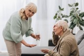 senior woman giving pills and glass of water to old man and looking at camera