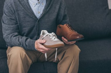 cropped view of senior man holding classic and modern shoes in hands