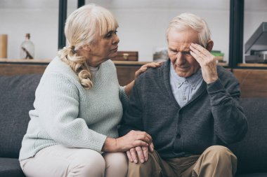 retired woman sitting near senior husband with headache