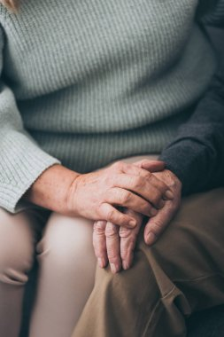 cropped view of retired woman holding hands with senior husband