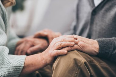 cropped view of retired couple holding hands