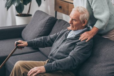 cropped view of senior wife hugging retired husband at home