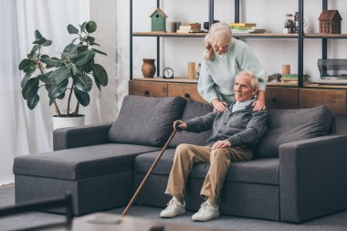retired wife embrace sad senior husband sitting with walking cane in living room