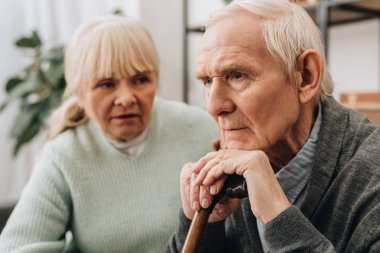 selective focus of sad pensioner sitting near senior wife at home