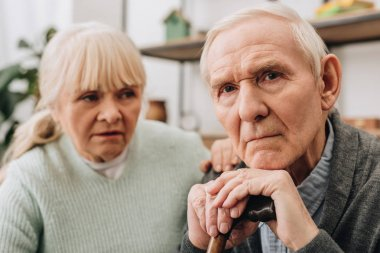 selective focus of sad pensioner sitting near retired wife at home