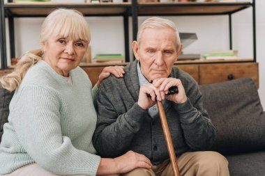 supportive senior wife sitting near retired husband with walking cane in living room
