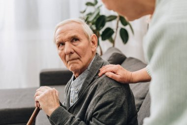 upset retired husband sitting in living room and looking at senior wife