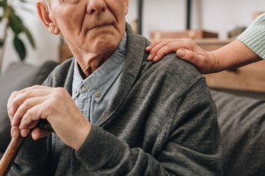 cropped view of sad pensioner with wife hands on shoulder