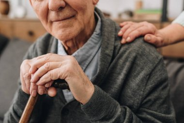cropped view of happy pensioner with wife hands on shoulder