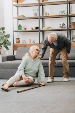 senior wife sitting on floor with pain in knee near retired husband