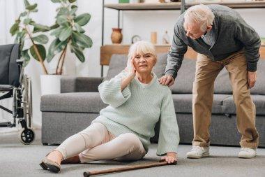 senior wife sitting on floor with headache near supportive retired husband