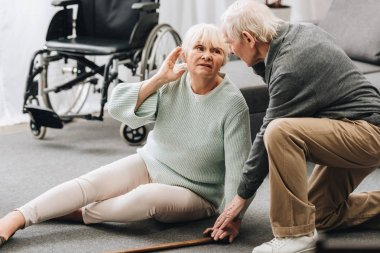 supportive retired husband looking at senior wife sitting on floor