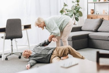 old woman helping to husband who falled down on floor