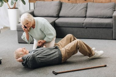 senior woman holding hand of dying old man with walking stick