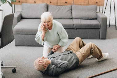 senior woman helping to husband who falled down on floor