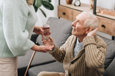 senior woman helping to old man with walking stick and giving pills