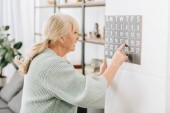 senior woman touching wall calendar and looking at dates