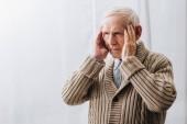 pensionato con la malattia di demenza avendo mal di testa a casa