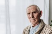 naštvaný muž v důchodu s šedými vlasy při pohledu kamery