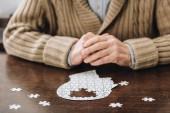 oříznutý pohled starší muž si hraje s hádanky na stole