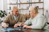 šťastný starší pár si hraje s puzzle doma