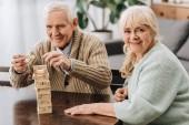 Glückliche Rentner spielen Jenga-Spiel auf dem Tisch