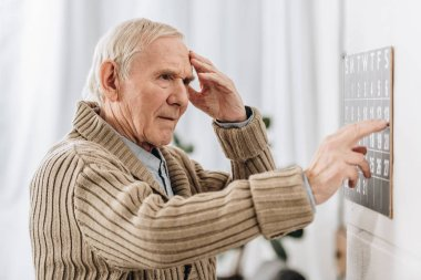 Senior man looking at wall calendar and touching head stock vector
