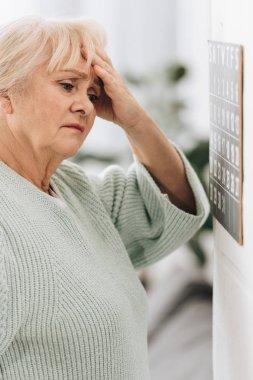 Upset senior woman looking at calendar on wall stock vector