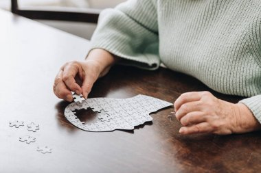 cropped view of senior woman playing with puzzles
