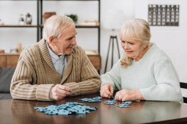 happy retired couple playing with puzzles at home