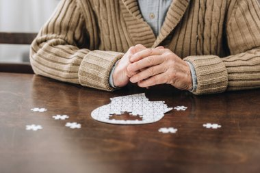 cropped view of retired man playing with puzzles on table