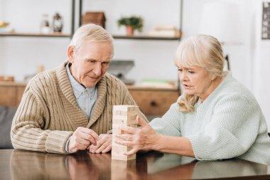 senior couple playing jenga game at home