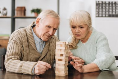 retired couple playing jenga game on table