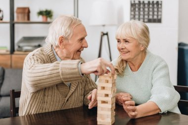 smiling pensioners playing jenga game on table